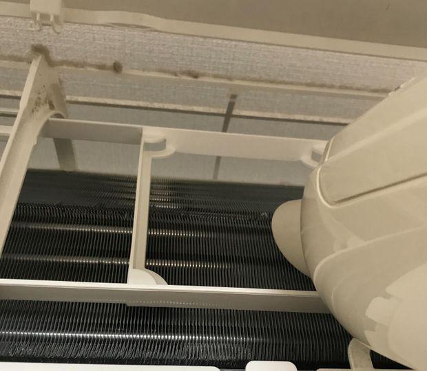 エアコンの冷却フィンのホコリを掃除機で吸い取る